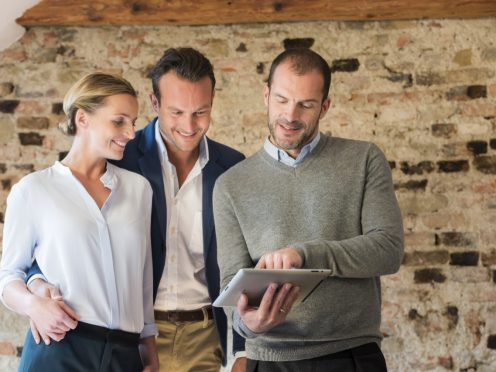 Architect presents project to couple on tablet in front of old brick wall