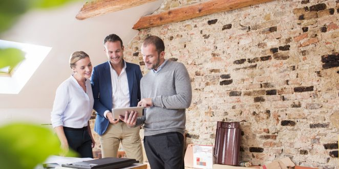 Architect with tablet presenting tablet to end customer at studio in attic loft
